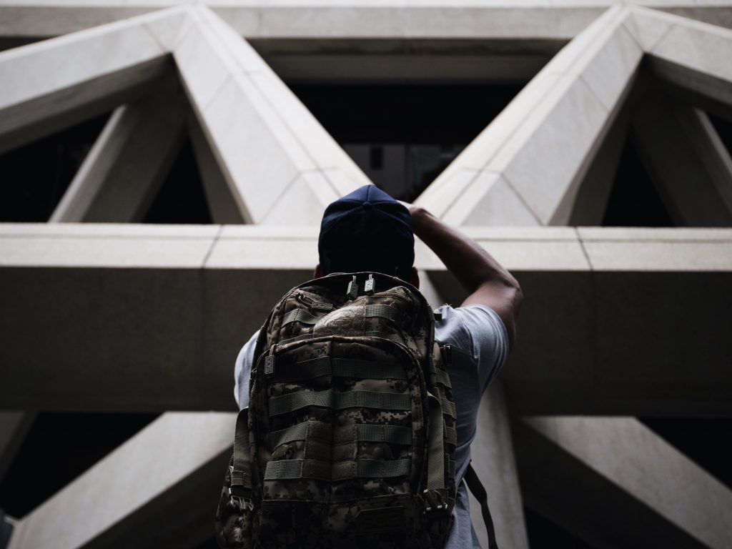 Un photographe devant un batiment en béton