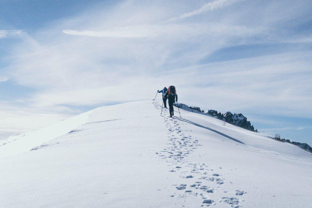 Deux randonneurs qui grimpent une montagne dans la neige