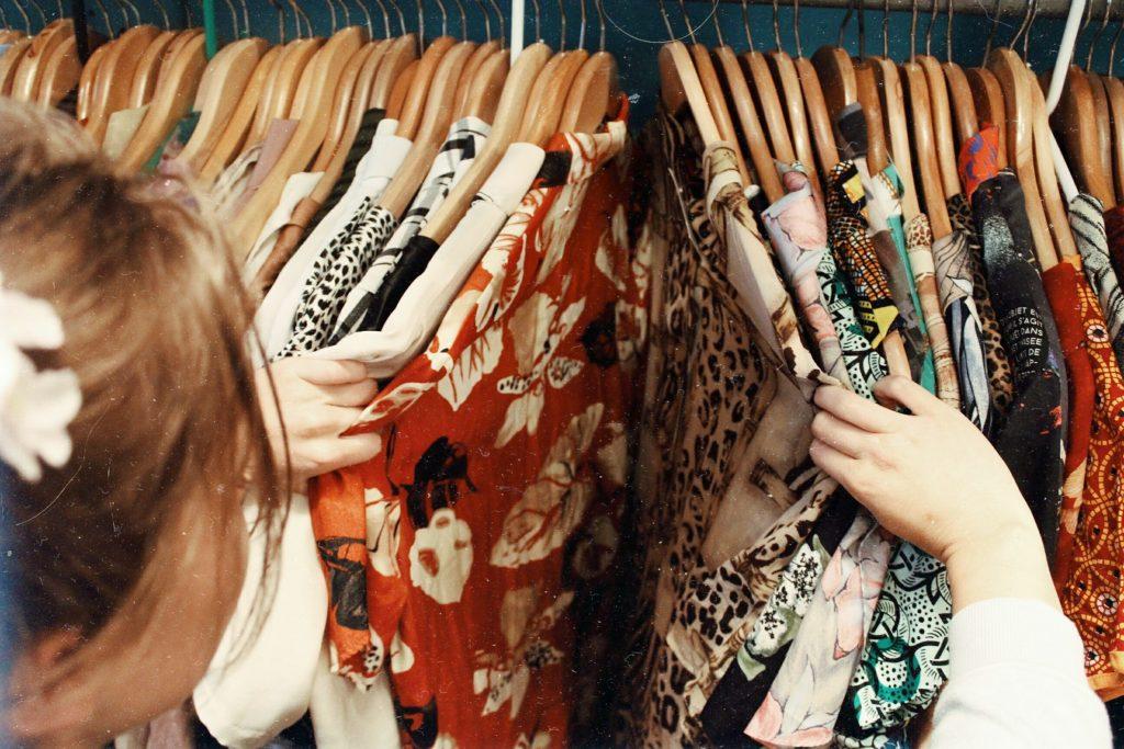 femme qui cherche des vêtements sur des portants